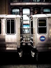 Couple (EMENFUCKOS) Tags: chicago transit authority public transportation couple chaings married cta logo steel massive light platform advertising bravo links rails electric lines chains springs windows sliding pull down trains lights rail 3rd step 4 ads advertisment building loop background offices post symmetry photography explore