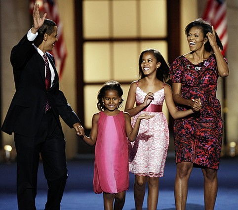Michelle Obama and daughters dressed up on stage