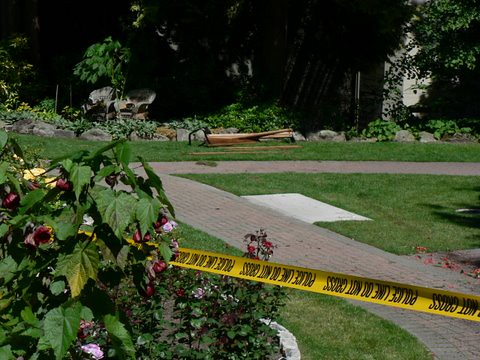 A destroyed bench is visible in the background, behind the police tape. Photo: Briana Tomkinson