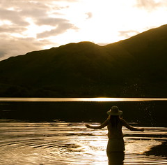 61/365 (Katie Lionheart) Tags: sunset lake water girl hat lensflare figure flare ripples waterdroplets thelakedistrict splashingwater crummuckwater