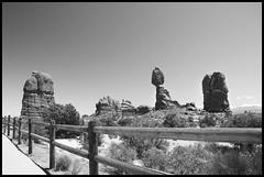 balancing rock. (zcrew) Tags: red sky blackandwhite bw west rock fence utah nationalpark ut desert arches moab southernutah redrock balancingrock balancedrock