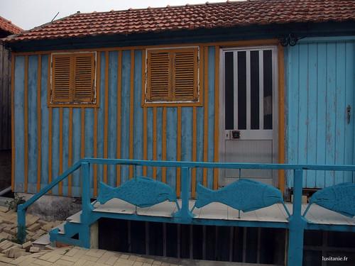 Casa azul, com uma porta de alumínio, e uma porta velha de madeira