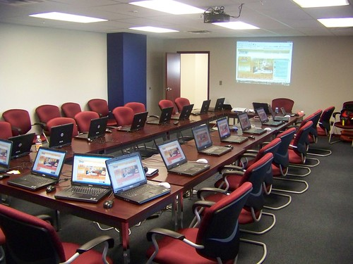 a square table surrounded by lots of chairs and laptops in a conference room.
