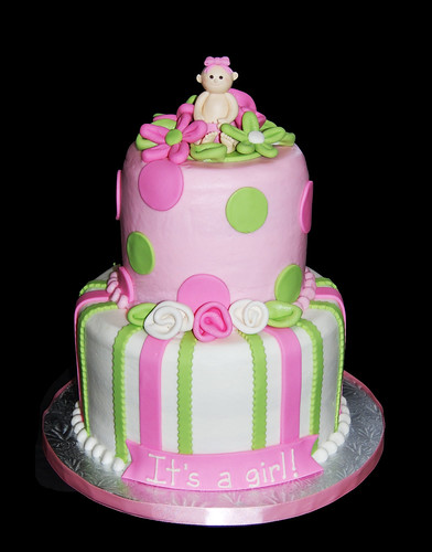 pink and green baby shower cake topped with a baby in a flower patch
