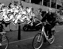 female police on a bike (wojofoto) Tags: bw woman streetart amsterdam bike graffiti police vrouw fiets zw politie bloemgracht serch wojofoto