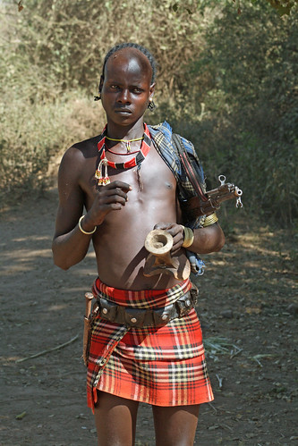 Murelle camp at the Omo River: herdsman with stool, skirt and AK-47