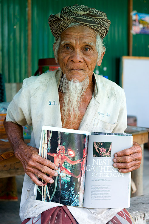Sahat, a bird nest gatherer from Ko Yao Noi, Thailand, holds a copy of the National Geographic article that features him