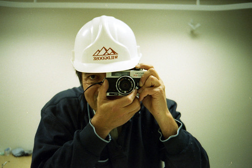 reflected self-portrait with Ricoh 500 GX and hard hat by pho-Tony