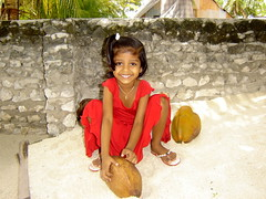 The whole world in her hands... (Island Chic) Tags: child innocence maldives beauty island coconut smile islands islandchic life beach sunny peaceful people dhivehi home beautiful blue summer travel trip pretty maldivian simple nature amazing maldive love blues shades sun sand sea vacation face portrait faces expression canon 500d slr dslr chic