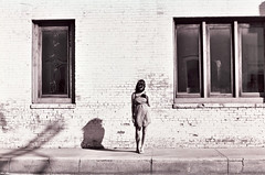 Small Town Beauty Queen. (The Vision Beautiful) Tags: windows shadow blackandwhite bw sun brick film girl beauty wall 50mm town small symmetry queen teen canonae1 harsh katyeskillman