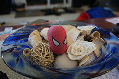 a bowl of random assorted items; recognizable: rubber band ball, spiderman head, large white flower, small white flower, shells, pine cone