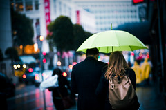 Untitled (SHUN [iamtekn]) Tags: sanfrancisco street urban blur green rain weather umbrella canon shopping bag shower blurry couple downtown gloomy bokeh 85mm purse 5d canon5d pouring canoneos5d shootwideopen canonef85mmf18usm tekn