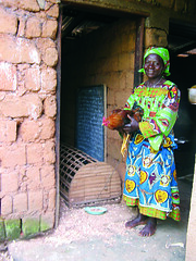 A grandmother of Bafut, Cameroon stands with her chicken at the entrance to one of the rooms of her home earlier this year. The hand-woven structure behind her is her chicken coop. ~photo courtesy St. Ann Center