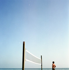 man, net, pacific ocean. (AAGCTT) Tags: california blue sky man 6x6 film beach mediumformat beachvolleyball pacificocean orangecounty minimalism expired lagunabeach hasselblad501cm sunnycalifornia c41 kodakportra100t carlzeissplanar80mmf28