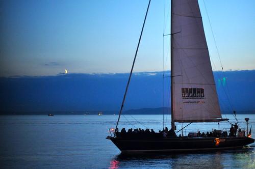 Sailboat passes the Moon