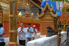 Men walking around the golden Dagoba completing a puja at Wat Doi Suthep