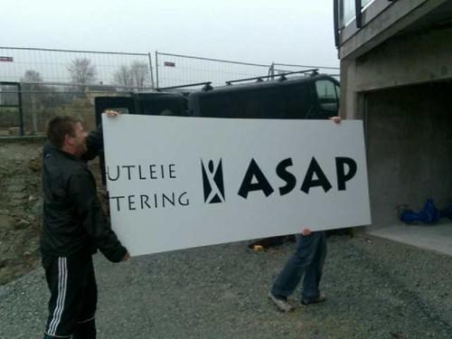 Her bærer Ingvar Haukelid, til venstre, og Ole Næss ett av de nye skiltene inn på lager i Staaltun-kjelleren.