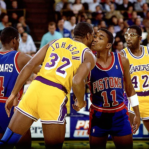 Johnson, left, and Thomas exchanging kisses before a game during the 1989 NBA Finals (Andrew Bernstein/Getty Images)