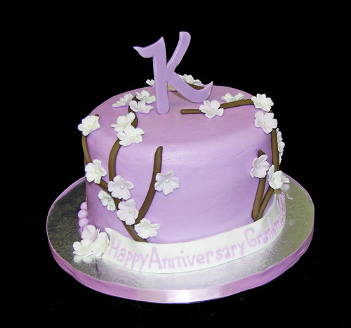 Lavendar Anniversary Cake with branches and flowers topped with a monogram