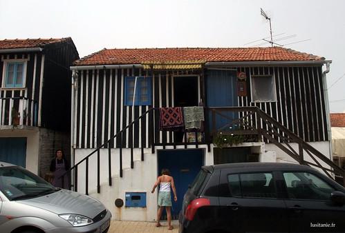 A casa é muito colorida, com a sua porta e a sua janela azuis, e as suas paredes às riscas