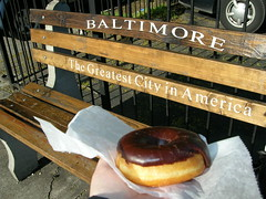 The Biggest Donut in America, just sitting there on a bench in Baltimore. (Zombie37) Tags: city urban food brown white scale america bench big funny flickr sitting text baltimore busstop eat snack donut doughnut huge gigantic happyaccident outsized thegreatestcityinamerica dayofthedonut waxpaer