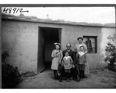 family seated in front of a house