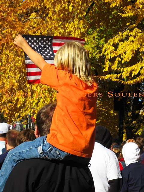 A young child on a father's shoulders holds up an American flag.