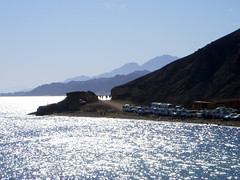 dahab. tiny camels, tiny cars (kexi) Tags: blue sea wallpaper mountains water nikon december afternoon dahab redsea horizon egypt silhouettes coolpix 2008 sparkling instantfave kartpostal thebestofday
