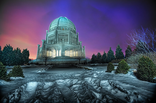 "The Bahai Temple at Blue Hour View Large on Black at <a href=""http://www.thewindypixel.com"" rel=""nofollow"">www.thewindypixel.com!</a>  ""Sometimes you just get lucky"": I've mentioned before how the light was relatively poor while I was photographing the Baha'i House of Worship in Wilmette. There was no sunrise and I missed the five seconds of great light by being on the wrong side of the building. Despite these setbacks, I came away with a few great images, predominately because the temple is simply stunning. I was taking a few photographs from whatever vantage points weren't blocked off by a winter's worth of deep freeze, trying for something specific.  Sometimes when you're trying really hard to do one thing (get a shot of the white stone temple silhouetted against a pitch black sky) you luck out and get something that is quite the opposite, but better than you could have hoped for. A low cloud ceiling, sodium vapor lights, tungsten white-balance, and a rather nasty bit of lens flare coming off the ridiculous front element of the 14mm all intersected to create some very beautiful colors and shapes in the sky behind the temple. This would be an all-time favorite of mine were the foreground to be more interesting. Perhaps I should drop it to black with a little photoshop magic …. :)"