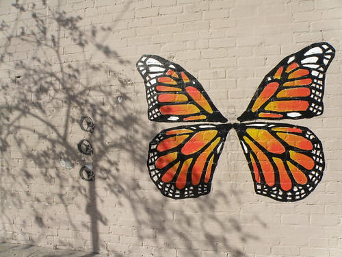 graffiti of intricately drawn Monarch butterfly wings, bright orange and black and white, on a beige-painted cement-brick wall