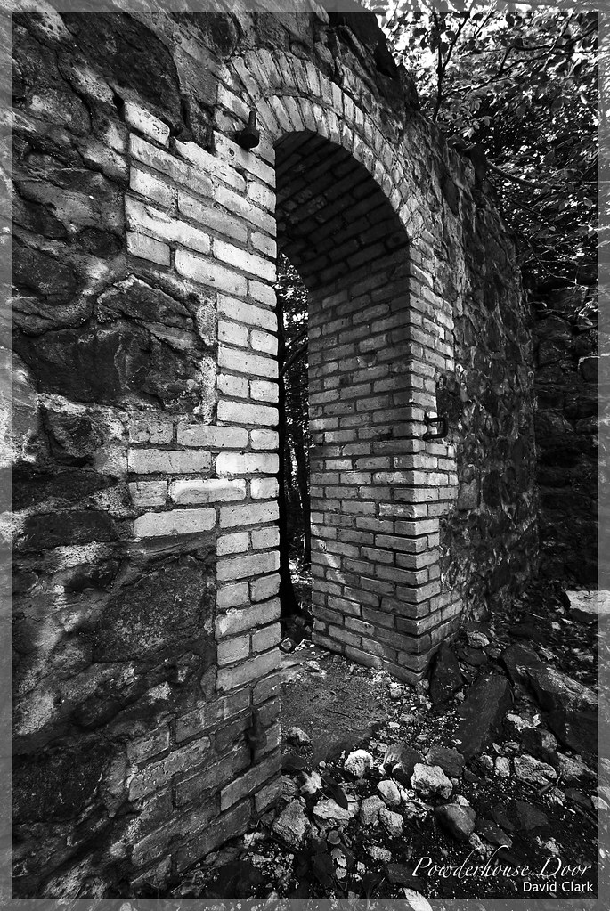 A wide angle shot of a brick  doorway in the middle of poor rock walls, all ruined.