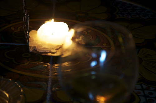 A glass of Scotch and a natural beeswax candle for light.