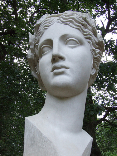 "Close-up of a white bust of Sappho titled ""Xth Muse"" by Ian Hamilton Finlay. It is mostly a smooth, nondescript face but has textured strands of short hair. Evening sun shines through a treetop in the background."