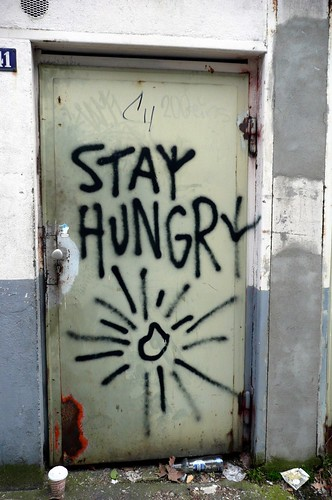 "image of a door with black, spray-painted graffiti, ""Stay Hungry"""