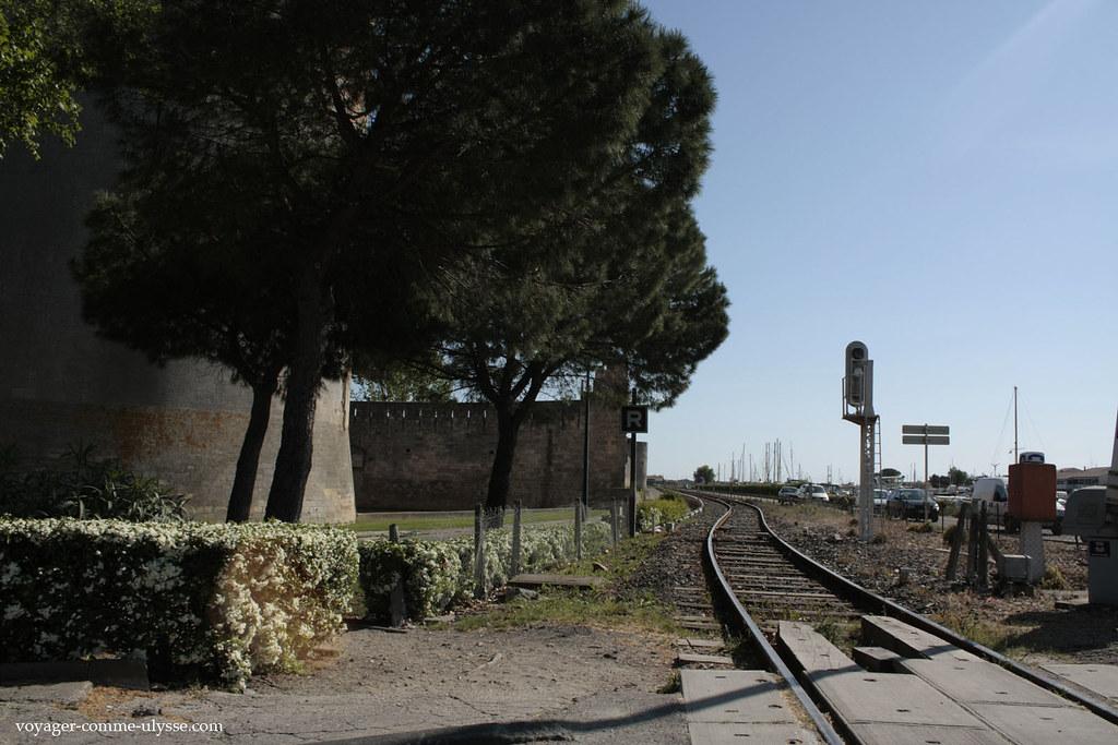 Une ligne de chemin de fer, entre les remparts de la ville et la route