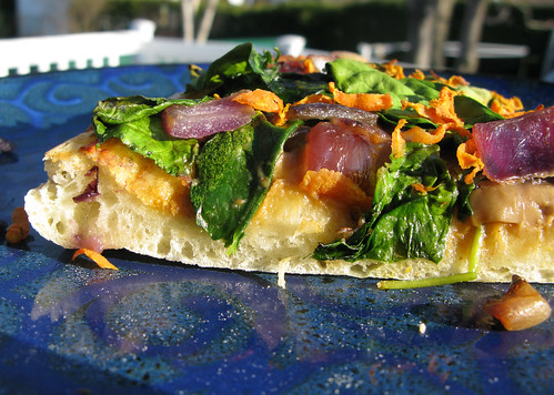 Caramelized onion and spinach pizza with a savoury peanut sauce...
