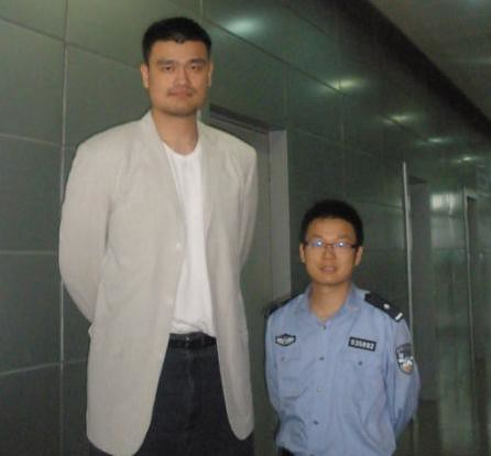 May 26, 2011 - Yao Ming poses with an immigration official at the Shanghai airport