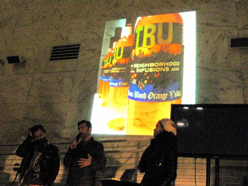 Matias and Austin stand before a bottle of their TRU vodka, the product of their Neighborhood Infusions project.