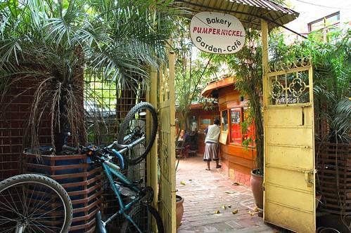 Pumpernickel Bakery Garden - Cafe gate, with bike parked outside, Kathmandu, Nepal by Wonderlane