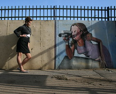 Zoo Fashion: Graffiti (Brenda Chenowith) Tags: camera shadow woman grass fashion fence pose graffiti purple perspective ground babe relationship lilac videocamera figure femalemodel isreal styling hotlegs businesswoman blackskirt silverearrings zoofashion