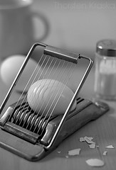 The Egg Slicer (Thorsten (TK)) Tags: lighting light shadow blackandwhite bw stilllife food shells white black utensils cooking cup kitchen metal reflections still raw shadows egg salt saltshaker eggs cooked simple ordinary kitchenware eggshells kitchengadget kitchenutensil foodphotography boiledegg eggslicer foodstyling eggcutter thorstenkraska