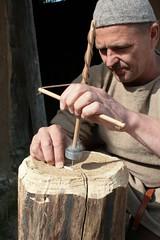 Christoph Roeser (hier mit einer Dreule) vor dem Haus des Kammmachers in Haithabu stellt aus Geweih eine Nadel her - Museumsfreifläche Wikinger Museum Haithabu WHH  06-06-2009