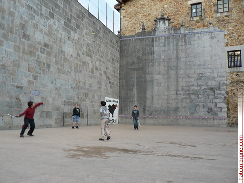 Des enfants jouent à la pelote basque sur le fronton attenant à la mairie d'Elorrio. Sur le mur à gauche, le drapeau réclamant la libération des prisonniers basques : « Euskal presoak, etxera! » (« prisonniers basques, à la maison! »). - Photo : N.Falcimaigne