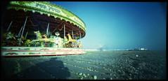 Whirl around (.scribe) Tags: 120 beach mediumformat pier seaside brighton fuji carousel panoramic pinhole merrygoround funfair brightonbeach provia vignette meandmyshadow brightonpier fromfilm palacepier 160 holgapinhole brightoncarousel notbrightonpier holgawpc holga120wpc holgawideanglepinhole holgawideangle