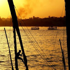 The magic of the Nile (... Arjun) Tags: africa sunset sky 15fav orange motion black topf25 silhouette yellow 1025fav 510fav river boats gold iso100 golden evening climb boat movement sailing ship action dusk smoke magic egypt silhouettes 100v10f move nile climbing 2550fav sail luxor f71 2009 felluca 105mm canonef24105mmf4lis bluelist fellucas neilos canoneos5dmarkii canon5dmarkii banksofluxor