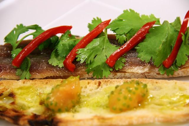 Detalle del Bocadillo de Sardinas Marinadas con Cilantro, Rajas de Jalapeño Rojo y Semillas de Tomate Bola