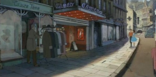 "The illusionist spies on Alice and her new boyfriend from behind a coat rack as they're walking down the street. It's sunny, and the characters are in front of a movie theatre called ""Cameo"". Alice is wearing a blue dress with white trim at the bottom, her boyfriend is wearing an orange shirt with dark pants, and the magician's clothes are dark."
