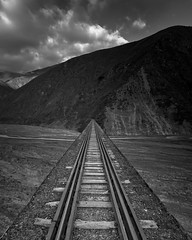 Vanishing Point (Ole Begemann) Tags: travel bw postprocessed latinamerica southamerica argentina lines clouds buildings dark landscapes vanishingpoint blackwhite reisen geometry bridges wolken 2006 rails sw 54 gebude landschaften brcken geometrie railwaytracks schienen linien nachbearbeitet argentinien lateinamerika trenalasnubes sdamerika schwarzweis fluchtpunkt saltaprovince camera:iso=100 quebradadeescoipe camera:model=canoneos20d lens:focallength=10mm camera:shutter=sec lens:aperture=f35 original:filename=2006051720d020996