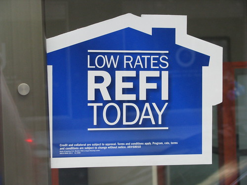 a blue sign advertising refinancing at low rates