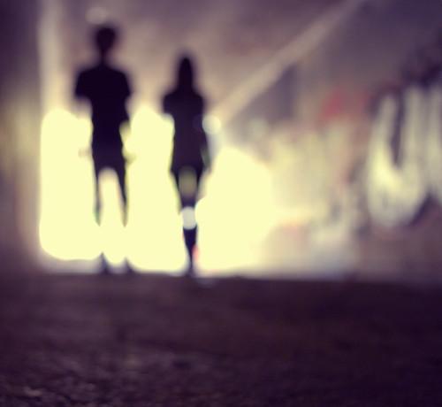 Fotografía de una pareja alejándose en un túnel con algunos grafitis hacia la salida